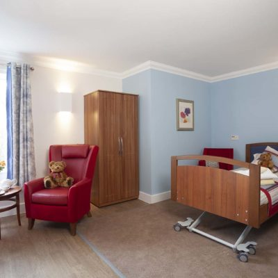 Bedroom with teddy bear and red chairs at Cedar View Care Centre Croydon